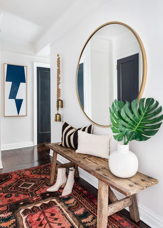 a boho chic entryway with a wooden bench, a boho rug, a wood frame round mirror plus bells hanging
