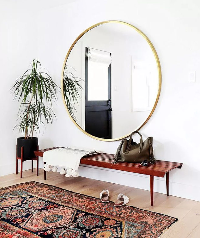 a boho chic entryway with a wooden bench, an oversized gold frame mirror, a boho rug and a potted plant