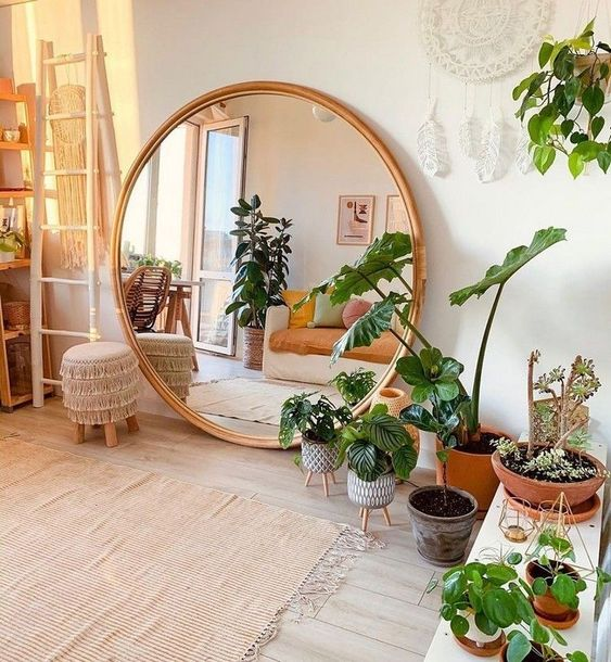a boho chic living room in neutrals, with lots of potted greenery and an oversized round mirror