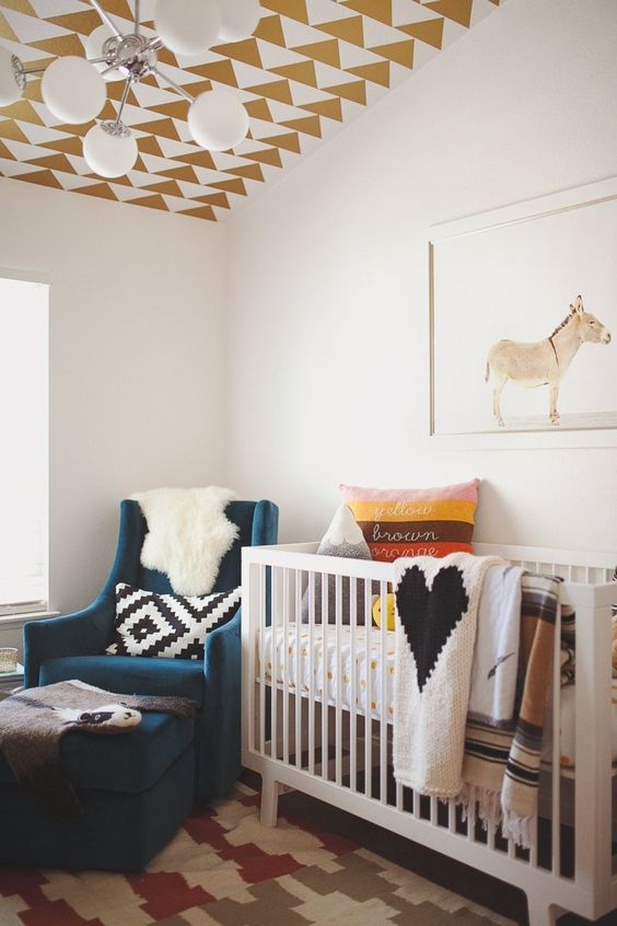 a boho kid's room with a gold geometric wallpaper ceiling, a graphic rug and pillow to make it bolder and cooler