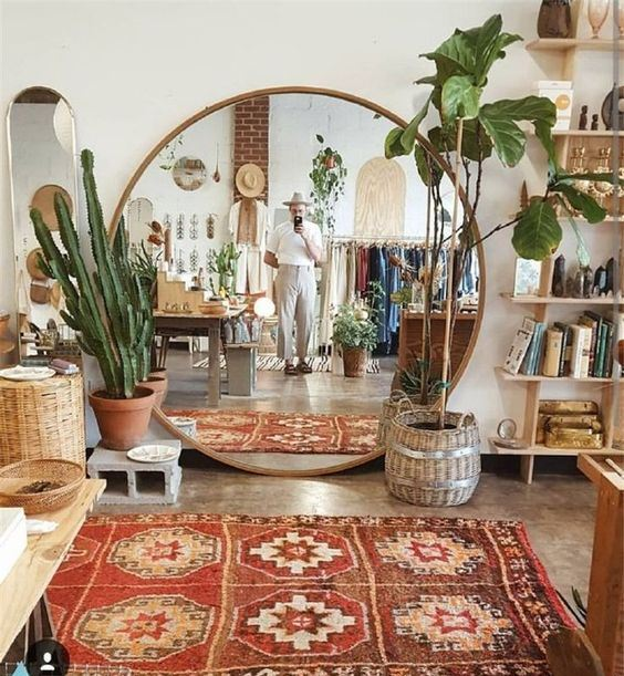 a boho living room with wooden and wicker furniture, potted plants, a boho rug and an oversized round mirror