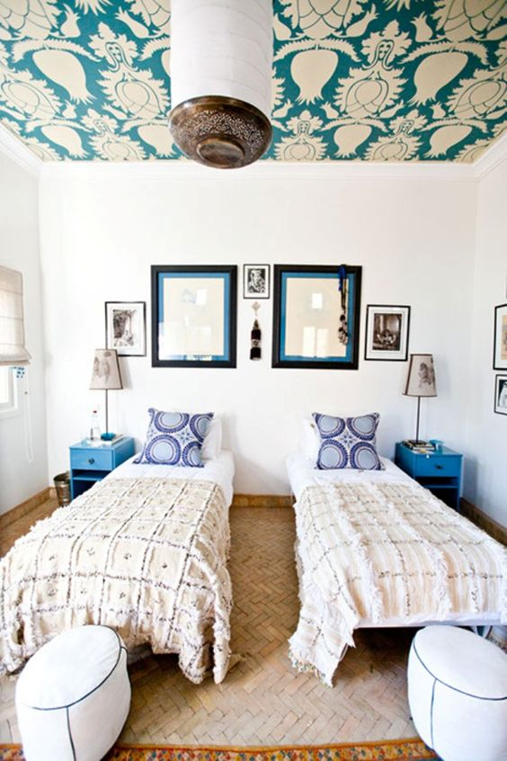 a bright double guest bedroom with a bright wallpaper ceiling, the prints of which match the pillows