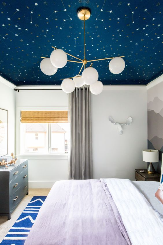 a celestial navy wallpaper wall makes the bedroom dreamy and trendy as everything celestial works