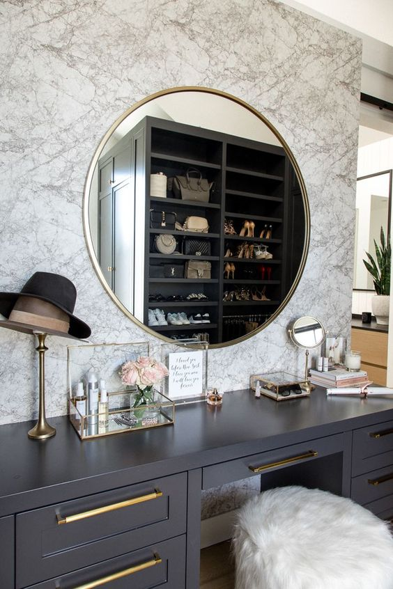 a chic closet with a makeup nook with a marble wall, a grey vanity, a gold frame mirror and many accessories