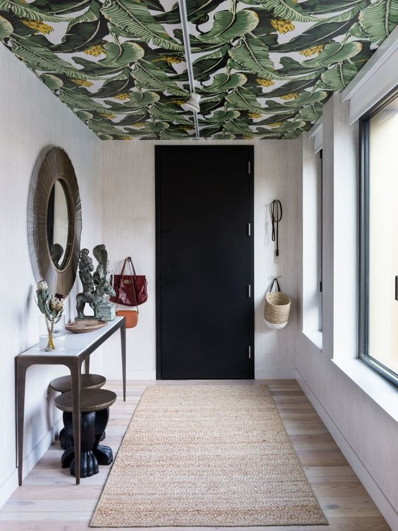 a chic entryway made bold with a banana leaf print wallpaper ceiling that adds print and color to make the space chic
