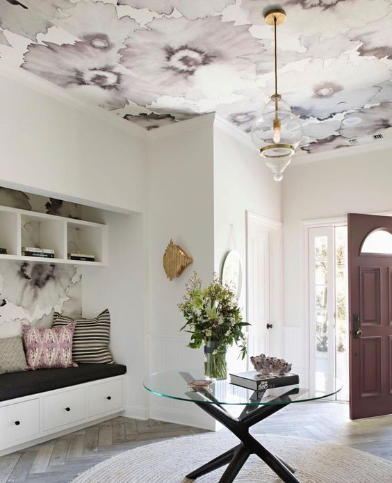 a chic entryway with a ceiling done with mauve floral wallpaper that echoes with the door and pillows