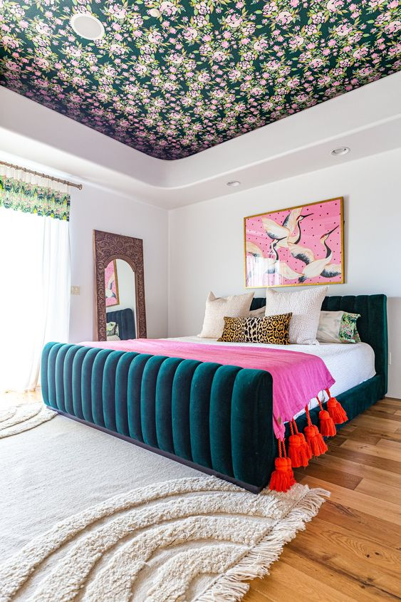 a colorful bedroom accented with a moody floral wallpaper ceiling that brings more print and evne more color to the space