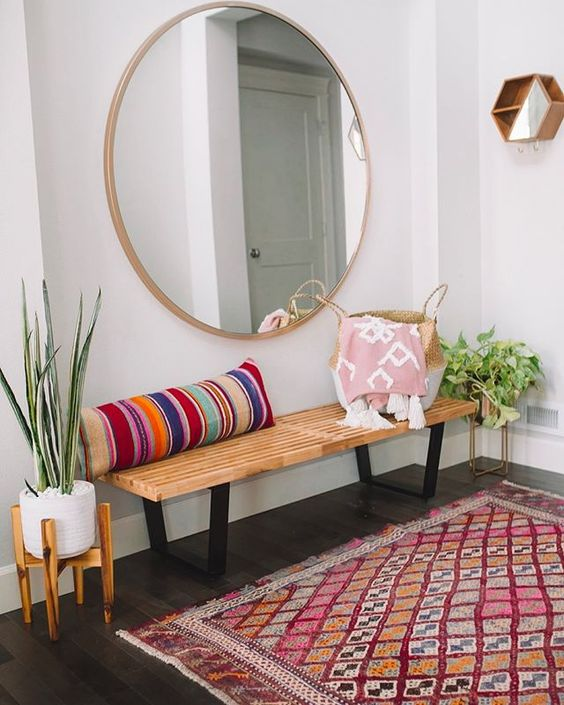 a colorful boho entryway with a wooden bench, a striped pillow, a round mirror, a bright rug and potted plants