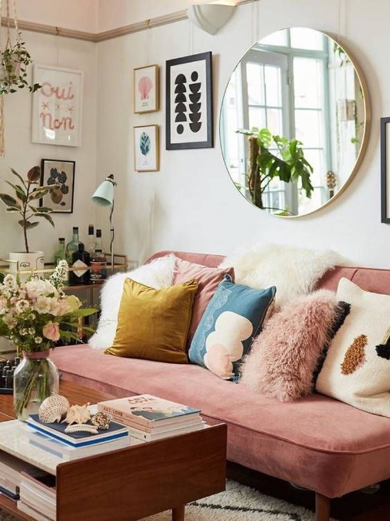 a colorful eclectic living room with a pink sofa, colorful pillows, potted plants, a gallery wall and a round mirror