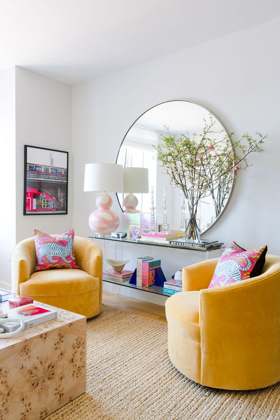 a colorful modern living room with neutral walls, yellow chairs, a slab table, an acrylic one and a round mirror