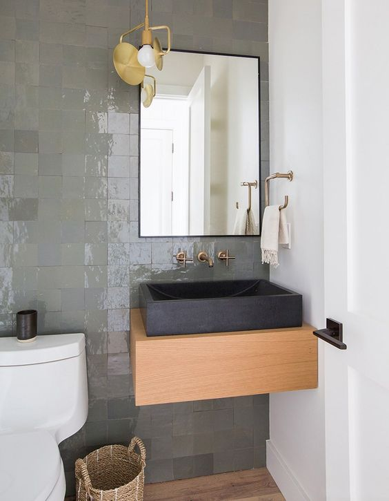 a contemporary bathroom with a shiny grene tile wall, a wooden vanity, a black square stone sink and a black framed mirror