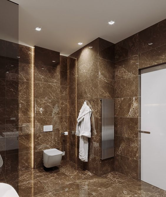 a contemporary brown bathroom clad with brown marble tiles, with white appliances and touches of stainless steel