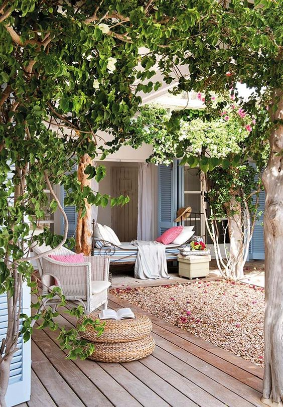 a cool backyard oasis with some trees, vines, a vintage daybed and rattan items plus pastel linens