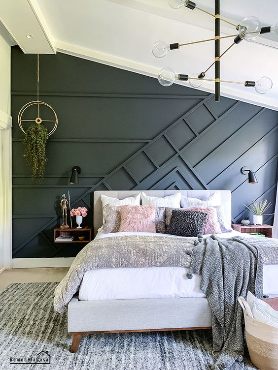 a cozy modern bedroom done in neutrals and with an accent black paneled wall that brings a bit of drama