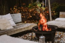 a fall backyard with wooden benches, faux fur, a fire pit and some pillows is super welcoming