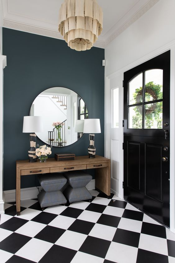 a glam art deco entryway with a wooden console table, grey stools, printed base lamps and a round mirror