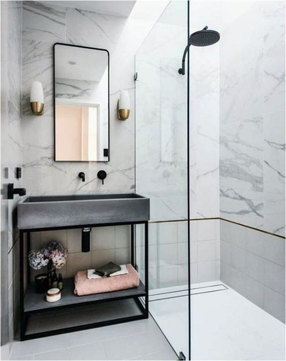 a glam bathroom clad with white marble, with tiles, a concrete sink and black fixtures to give it a fresher modern feel