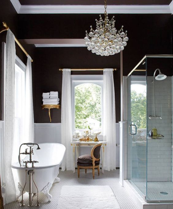 a glam bathroom with chocolate walls, white paneling, a vintage tub, a chic crystal chandelier and vintage furniture just wows