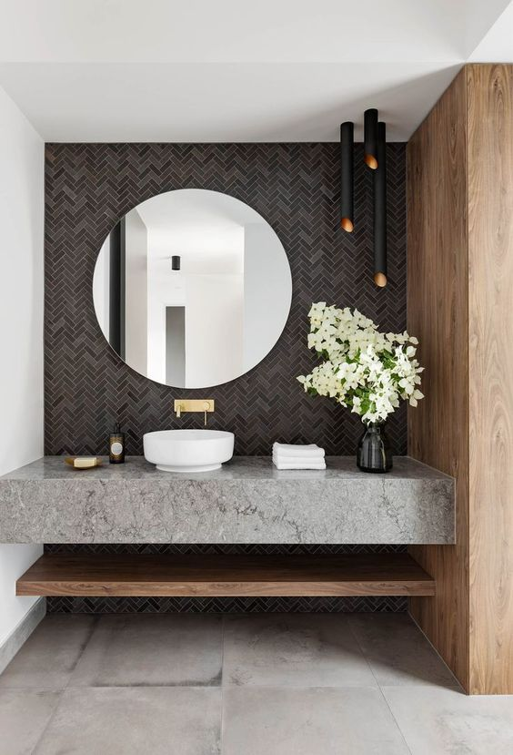 a gorgeous modern bathroom with a grey tile wall, black lamps, a grey stone vanity and a round mirror