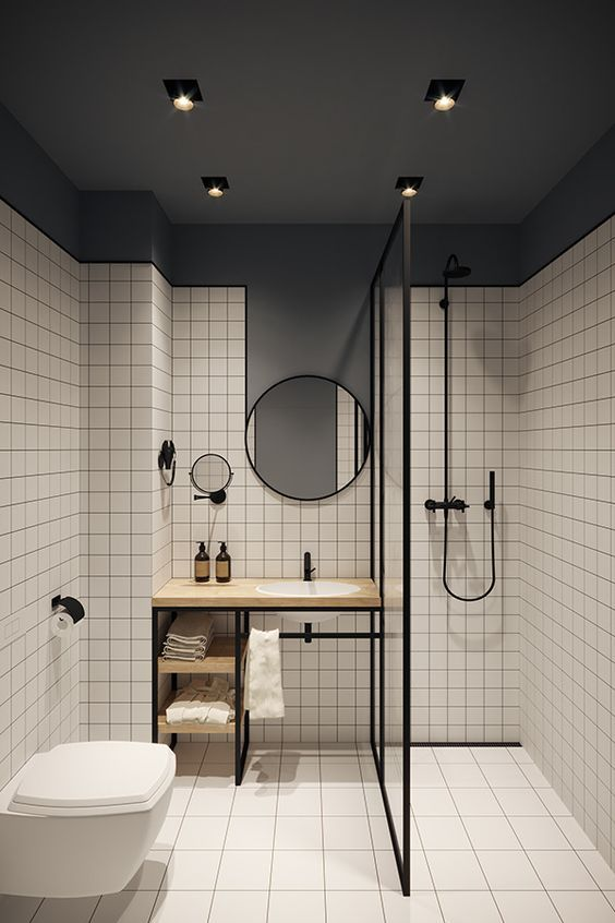 a grey and white bathroom accented with black edges, fixtures and mirror frames looks more modern and bolder