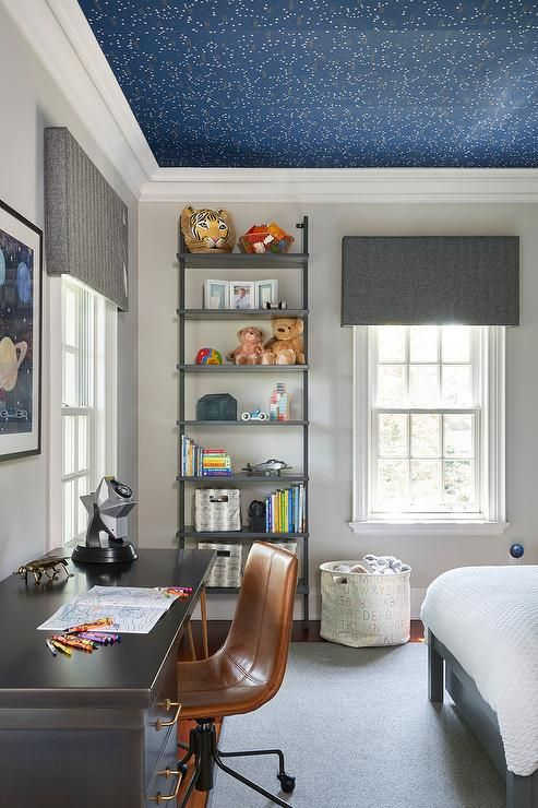 a kid's room with a navy celestial wallpaper ceiling that makes the space more dreamy and beautiful