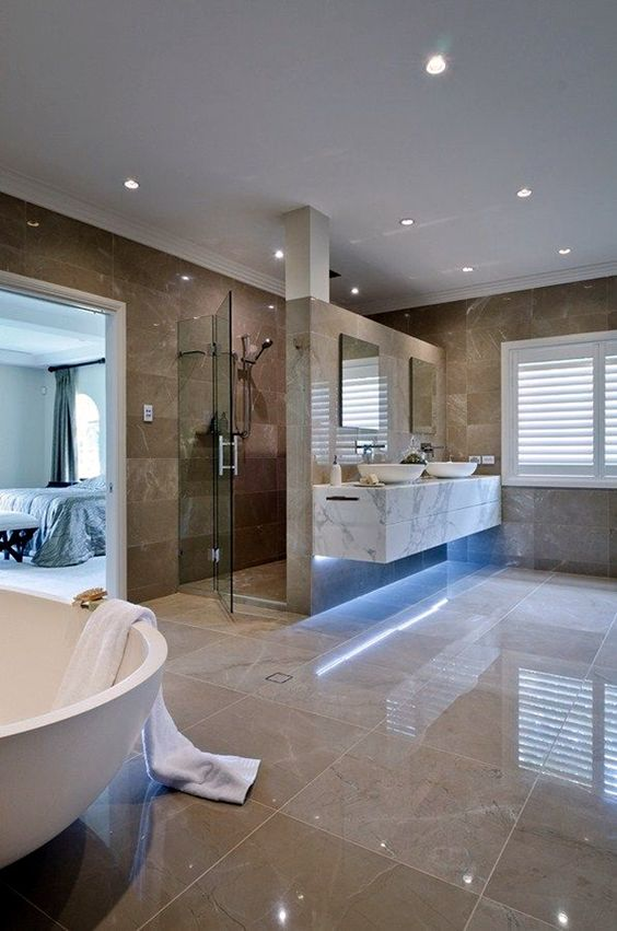 a large luxurious bathroom with tan and brown tiles, built-in lights, white appliances and a marble vanity