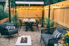 a mid-century modern backyard with gravel, a fire pit, black rattan furniture and lights all along the fence