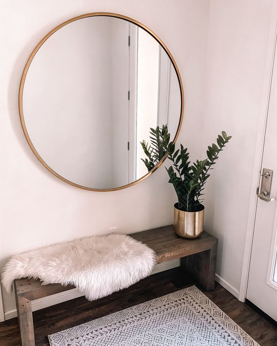 a minimal boho entryway with a wooden bench, a printed rug, a faux fur cover and a potted plant plus a round mirror