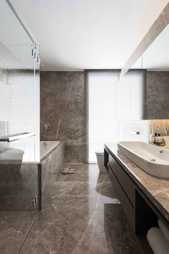 a minimalist bathroom clad with brown marble, with a logn sleek vanity and a marble clad bathtub is chic