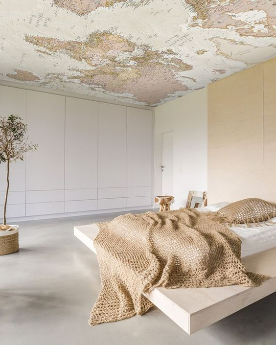 a minimalist bedroom with a map on the ceiling to dream where to go while lying in the bed