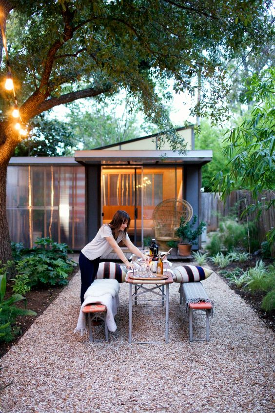 a modern backyard with greenery and trees, wooden and metal benches and a dining table plus striped pillows