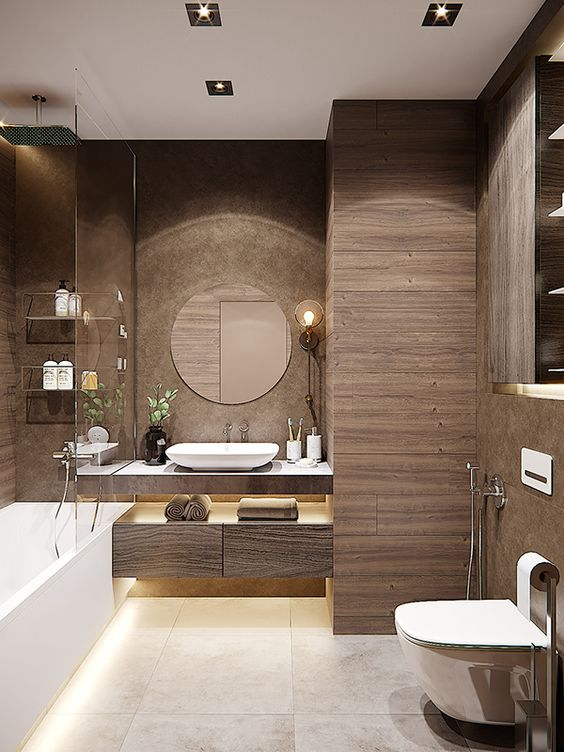 a modern brown bathroom clad with wood-like tiles, a floating vanitu and a storage unit, white appliances