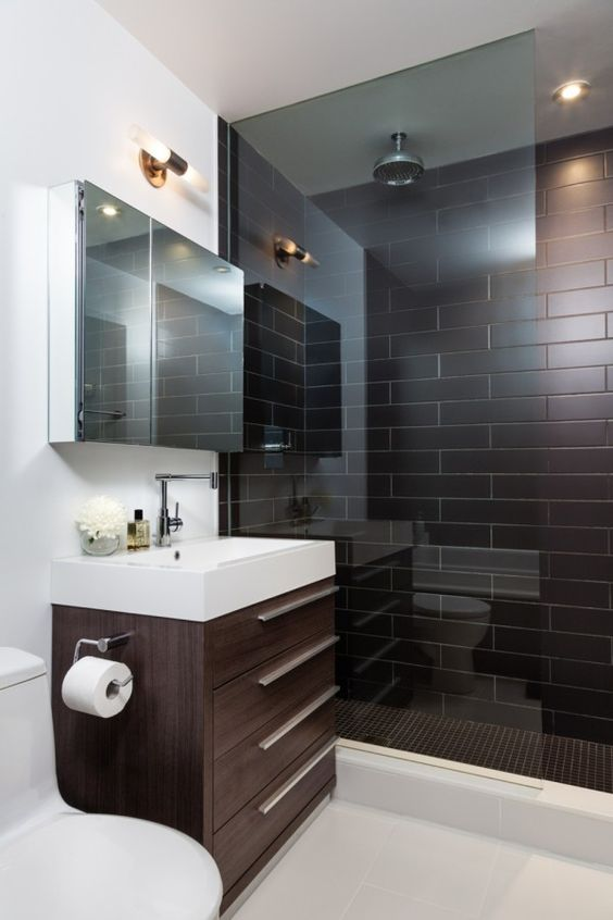 a modern chocolate brown and white bathroom with brown tiles in the shower, a brown vanity and white appliances and walls