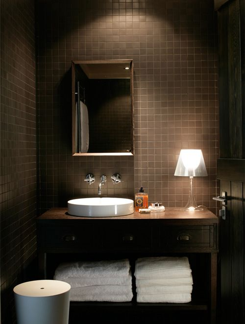 a modern chocolate powder room with tiles all over, a wooden vanity and touches of white, appliances and towels