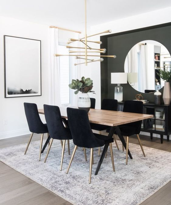 a modern glam dining room with a grey accent wall, a large round mirror, a catchy chandelier and black chairs