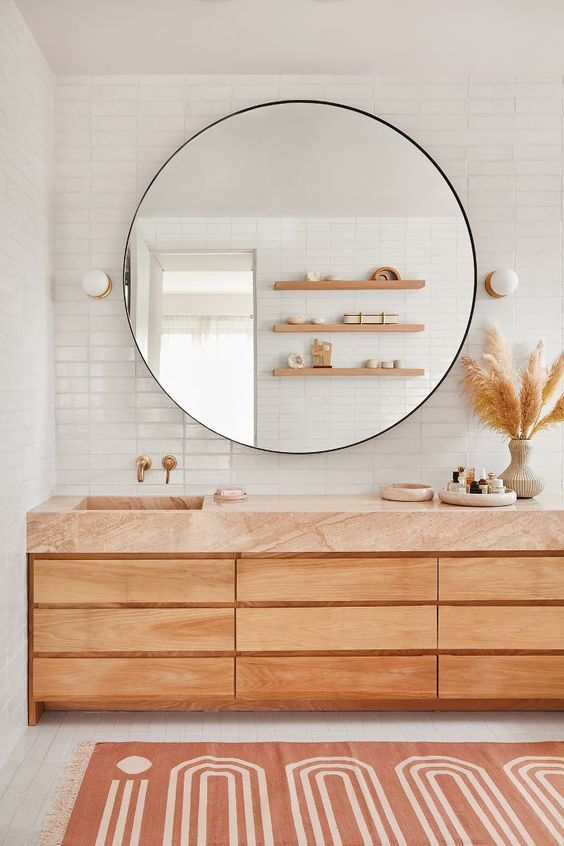 a modern natural bathroom with white tiles, a wooden vanity with a terracotta top and a large round mirror over it