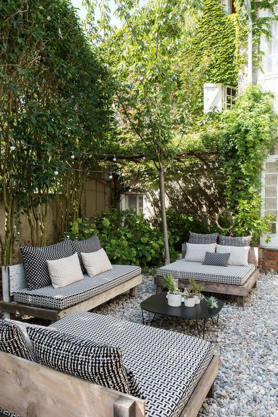 a monochromatic backyard with black and white furniture and lots of greenery around