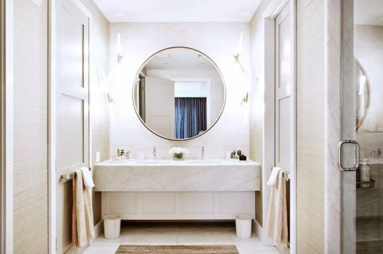 a neutral bathroom clad with white marble, with neutral walls and an oversized lit up round mirror to make the space even brighter