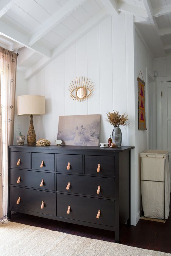 a neutral bedroom accented with a black dresser with leather pulls that highlights the color scheme and makes it cooler