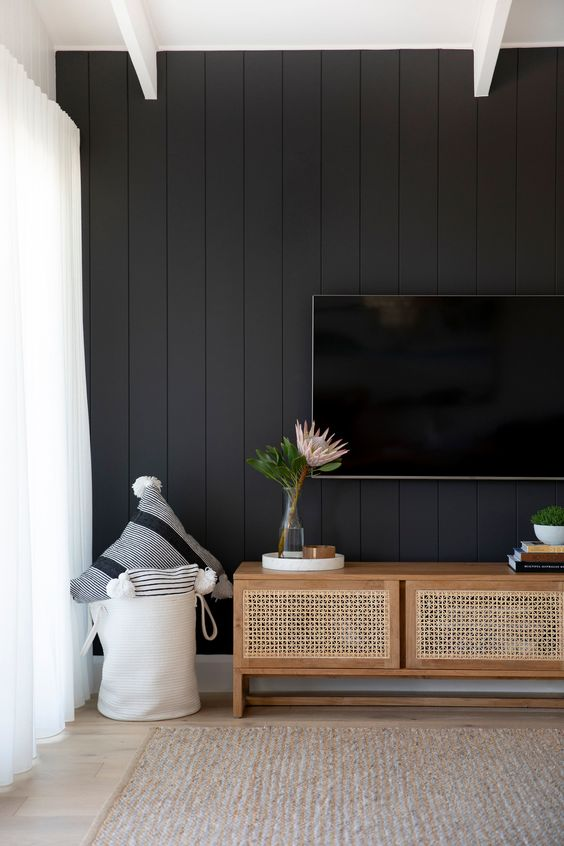 a neutral living room with a black beadboard wall for a bold and contrasting statement in the interior