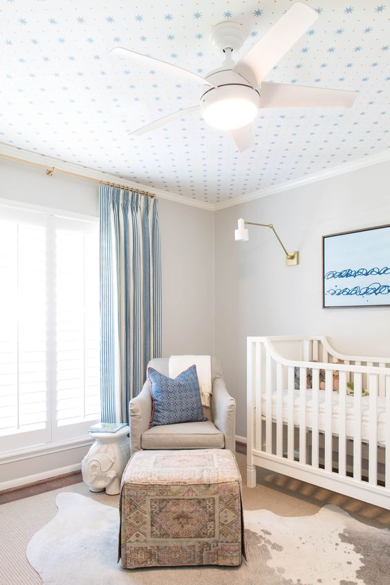 a rather neutral blue and white kid's room made cooler with a printed wallpaper ceiling that adds catchiness to the room