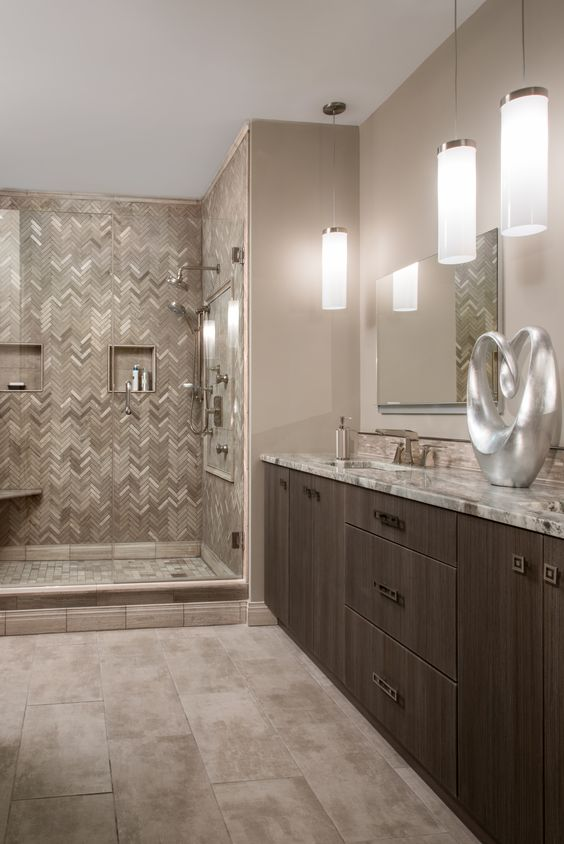 a refined bathroom with tan walls, a dark stained vanity, a tiled shower space and much stone