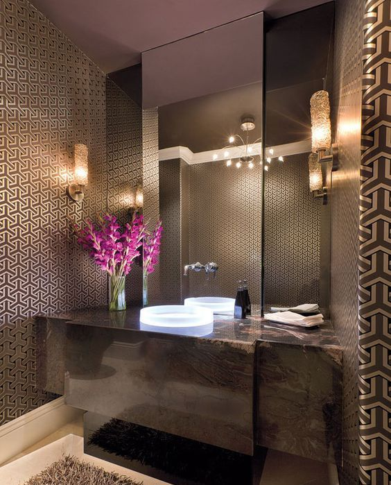 a refined brown bathroom with chic wallpaper, a brown marble vanity, a fluffy rug and a statement mirror
