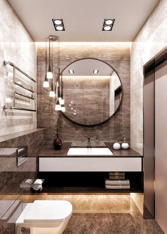 a refined brown bathroom with tiles, built-in lights, pendant lamps and a round mirror
