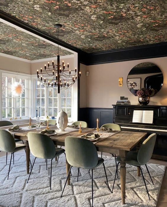 a refined dining room with a dark floral wallpaper ceiling that echoes with the chairs in color