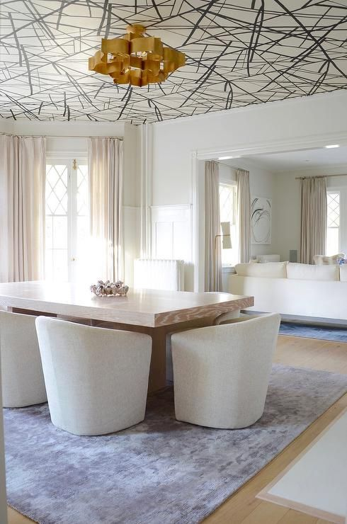 a refined dining space made bolder and edgier with graphic wallpaper on the ceiling