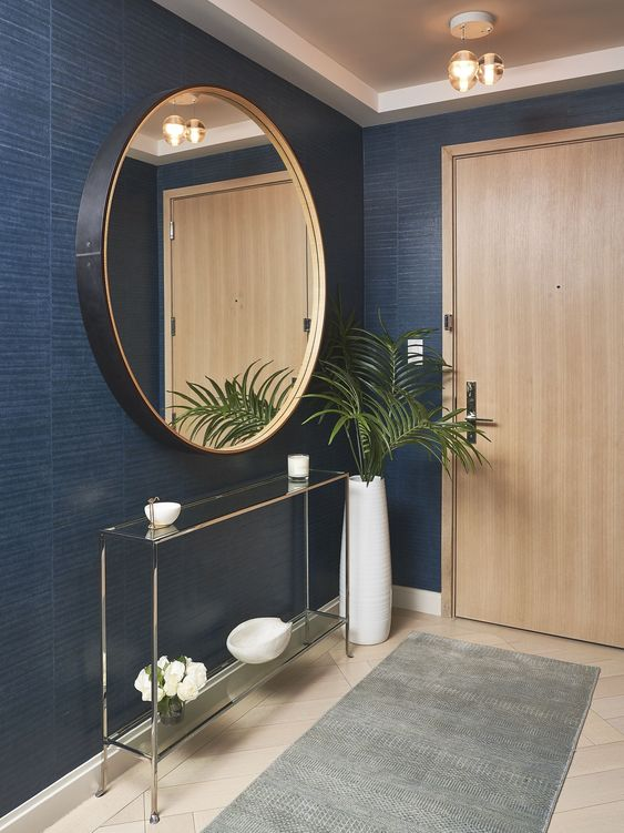 a refined modern foyer with navy walls, a glass console, a black frame round mirror and a plant in a vase