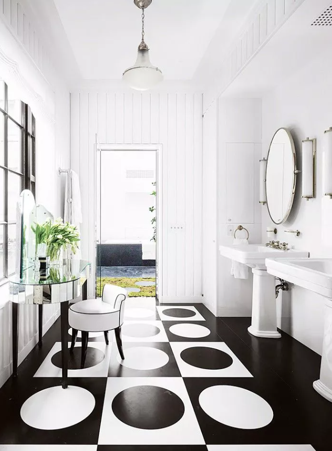 a refined monochromatic bathroom with white beadboard walls, white free standing sinks and an oversized white frame mirror