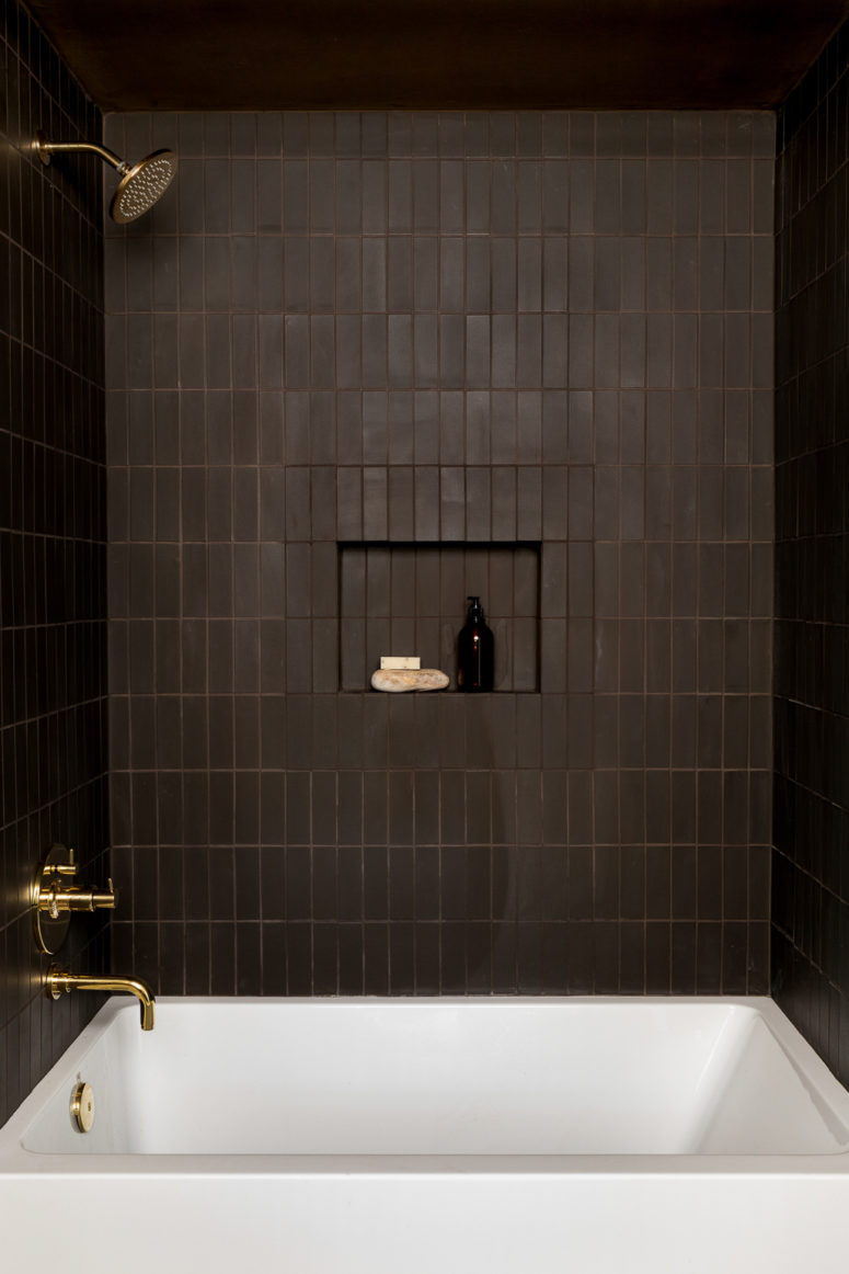 a refined moody bathroom clad with chocolate brown tiles, with chic gold fixtures, a white tub and a niche for storage