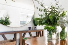 a rustic entryway with a wooden console and table, with baskets, an oversized round mirror and lots of greenery